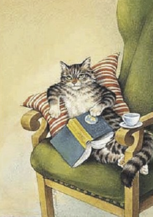 Reading cat reclined in chair with coffee